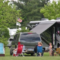 family at campsite sitting outside of camper